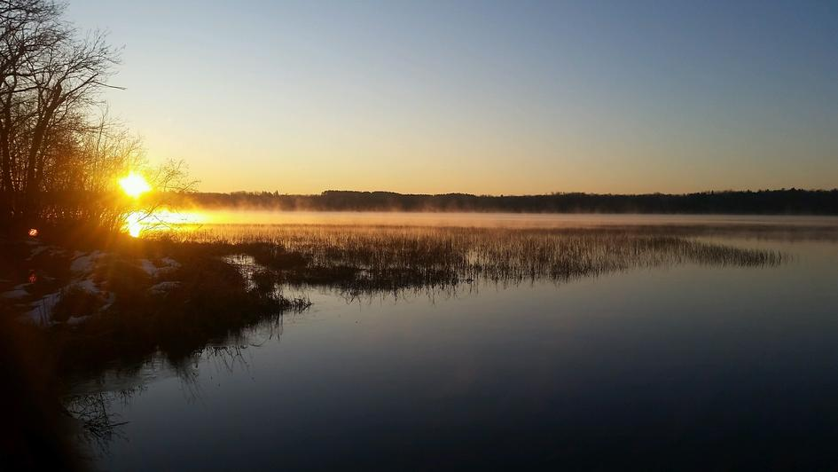 Steam coming out of the water and sun rising over Big Hanging Horn lake in Barnum