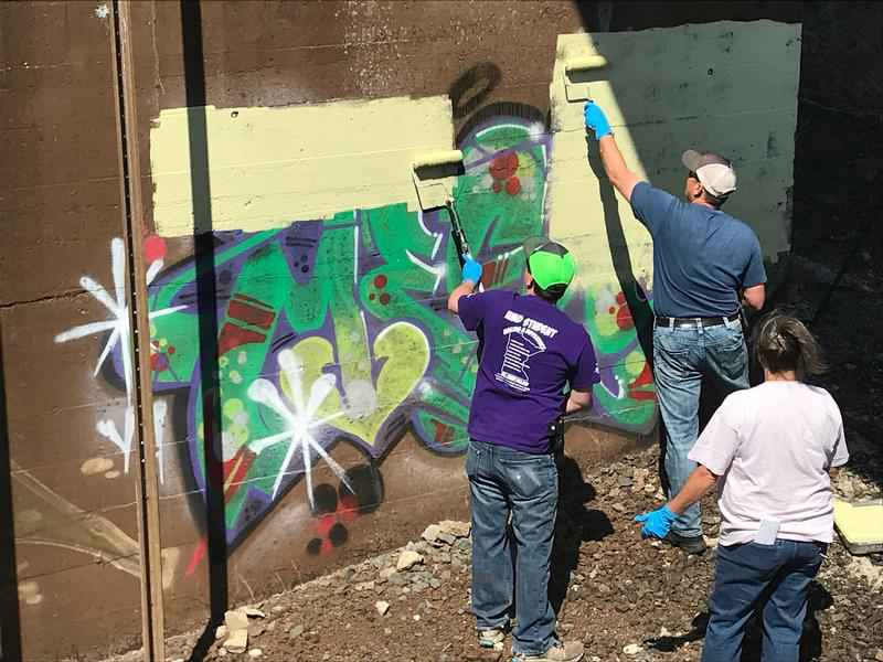 Volunteers paint over graffiti near the Oliver Bridge.