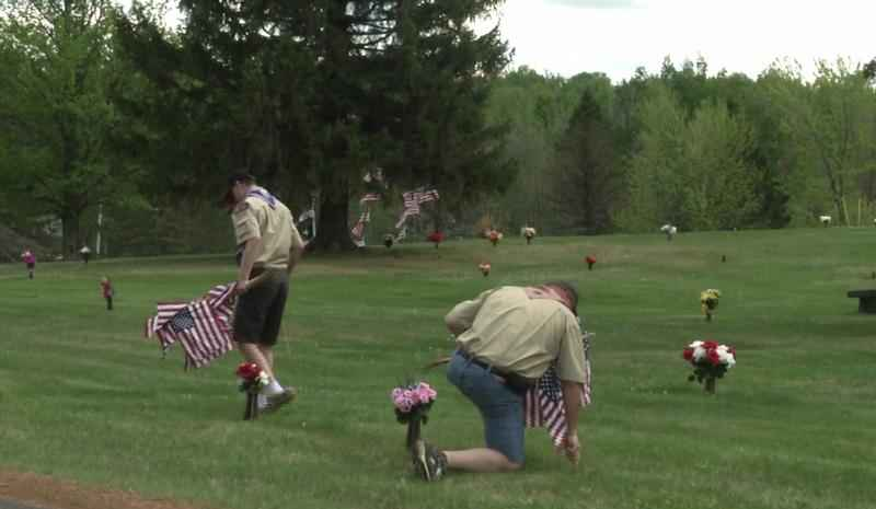 Boy scouts place flags on veterans graves at Sunrise Memorial Park.