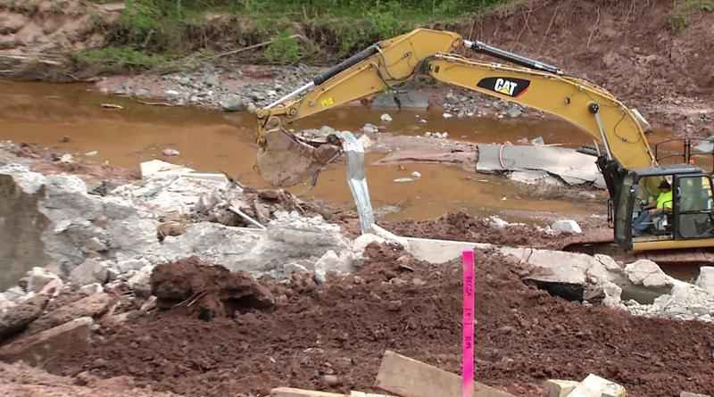 Work began Monday on US Highway 2 to replace the washed-out culvert with a new bridge.