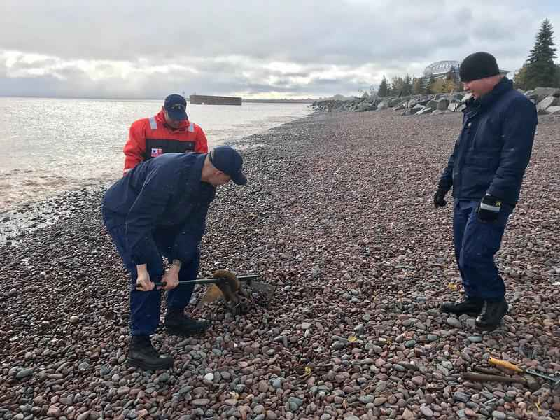 Coast Guard members pry up a 500-pound anchor that washed ashore.