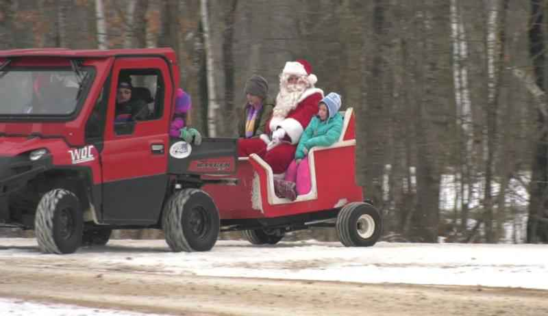 Santa rides in a sleigh behind an ATV with two kids.