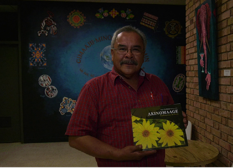 Vern Northrup posing with his new book, Akinomaage.