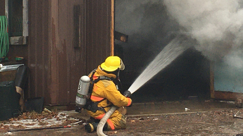 Firefighter from Cook works to put out a fire in the Maintenance building at Elbow Lake Lodge.