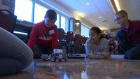 Three students watch to see if their rover successfully moves all the rocks out of the circle.