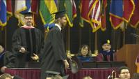 Rob Bordson crossing the stage during UMD's 2019 spring commencement ceremony.